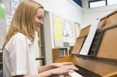 schoolgirl-playing-piano-in-music-class_rki13aths