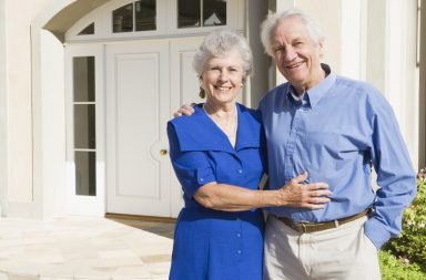 senior-couple-standing-outside-house_rkbvurahi