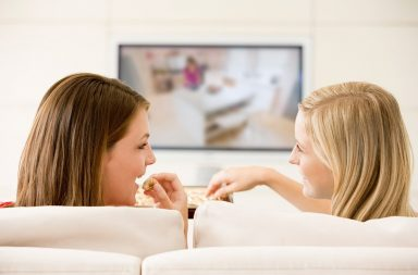 two-women-in-living-room-watching-television-eating-chocolates-smiling_ryhjwnahi