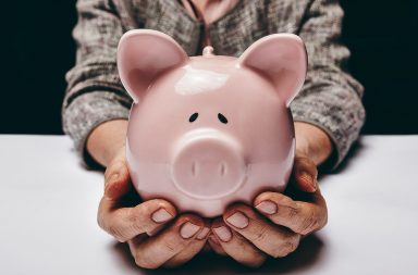 close-up-shot-of-elderly-woman-holding-pink-pig-money-box-senior-woman-hands-holding-a-piggybank-concept-of-saving-money-for-old-age_rpb4bduntx