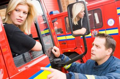 firefighter-sitting-in-the-cab-of-a-fire-engine-talking-to-a-co-worker_rtgj8acbo-resize