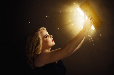 woman-holding-a-magic-book-with-lights_sxlx7kfxc