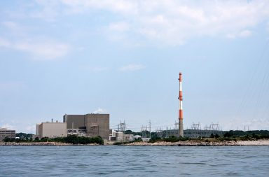 a-nuclear-power-plant-with-large-smoke-stack-and-high-power-lines_rkweki0si