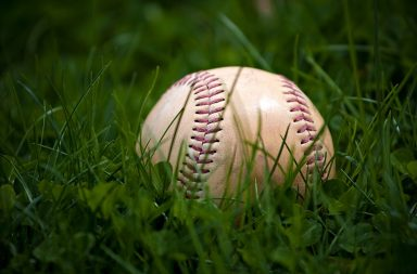 one-aged-and-worn-baseball-sitting-in-the-green-grass_rtmvpdrss