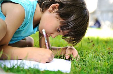 young-boy-outdoors-on-the-grass-writing_rk_qmdtbo