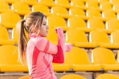 portrait-of-a-young-sports-woman-stretching-hands-at-stadium_sf6rt5abo-2