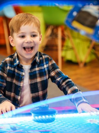 graphicstock-cheerful-little-boy-playing-air-hockey-and-having-fun-at-indoor-amusement-park_bda1f1v2x