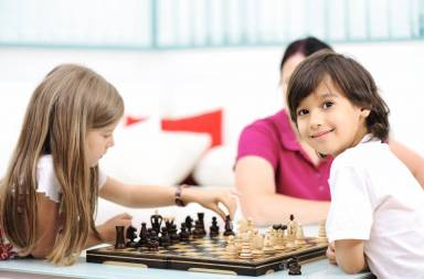 brother-and-sister-playing-chess-at-home-with-their-mother_byqnp56hj