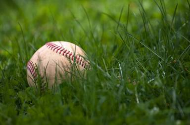 one-aged-and-worn-hardball-or-baseball-laying-in-the-green-grass_bymupwars