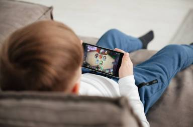 graphicstock-back-view-photo-of-little-boy-holding-smartphone-and-playing-game-while-sitting-on-sofa-at-home-look-at-phone_bdfad