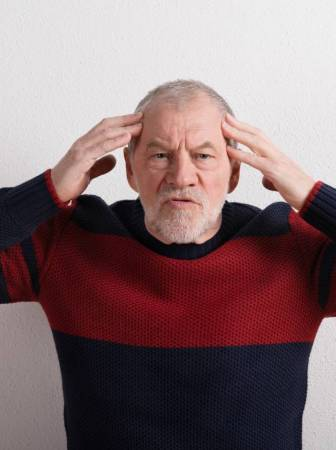 graphicstock-angry-senior-man-in-red-and-blue-sweater-holding-head-studio-shot-against-white-wall_bdksufufz
