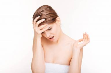 woman-with-headache-holding-pills-isolated-on-a-white-background_htilo2abs