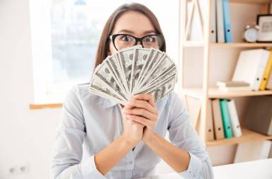 graphicstock-picture-of-businesswoman-dressed-in-white-shirt-sitting-in-her-office-and-holding-money-in-hand-near-face_r8ntfymdn
