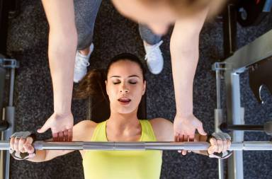 graphicstock-woman-with-her-personal-trainer-in-a-gym-working-out-with-weights-bench-pressing_h_8humrzb