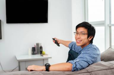 graphicstock-young-asian-man-in-shirt-watching-tv-on-sofa-looking-at-camera_huxtkpzw3g