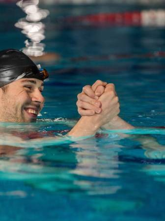 storyblocks-close-up-of-happy-male-swimmer-shaking-another-swimmers-hand-in-a-swimming-pool_b0moykha9w