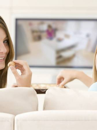 two-women-in-living-room-watching-television-eating-chocolates-smiling_hy9yz3arj