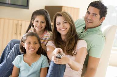 family-in-living-room-with-remote-control-smiling_hfgcun0bo