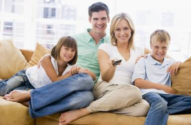 family-sitting-in-living-room-with-remote-control-smiling_htlb5horrs