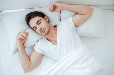graphicstock-top-view-of-attractive-young-man-lying-and-sleeping-in-bed_h_gjksau3l