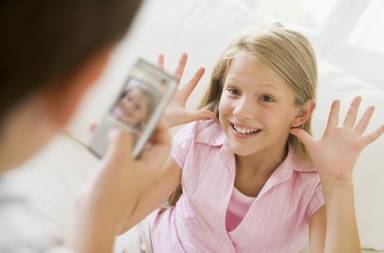 young-boy-taking-picture-of-smiling-young-girl-with-camera-phone-indoors_bfrevscbs