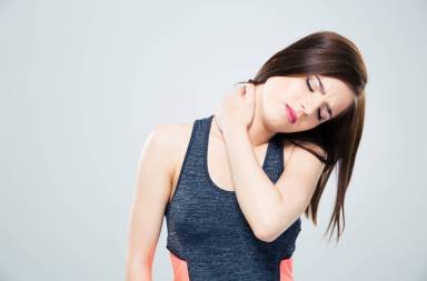 fitness-young-woman-with-neck-pain-over-gray-background_htzqs8aho
